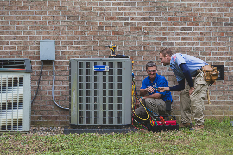 Technicians working on one of a a customers HVAC systems