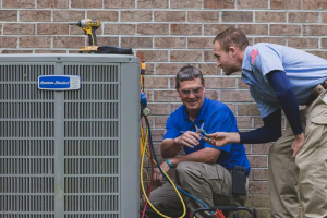 closeup - two hvac technicians employed by Casey Services working on an American Standard brand AC unit outside