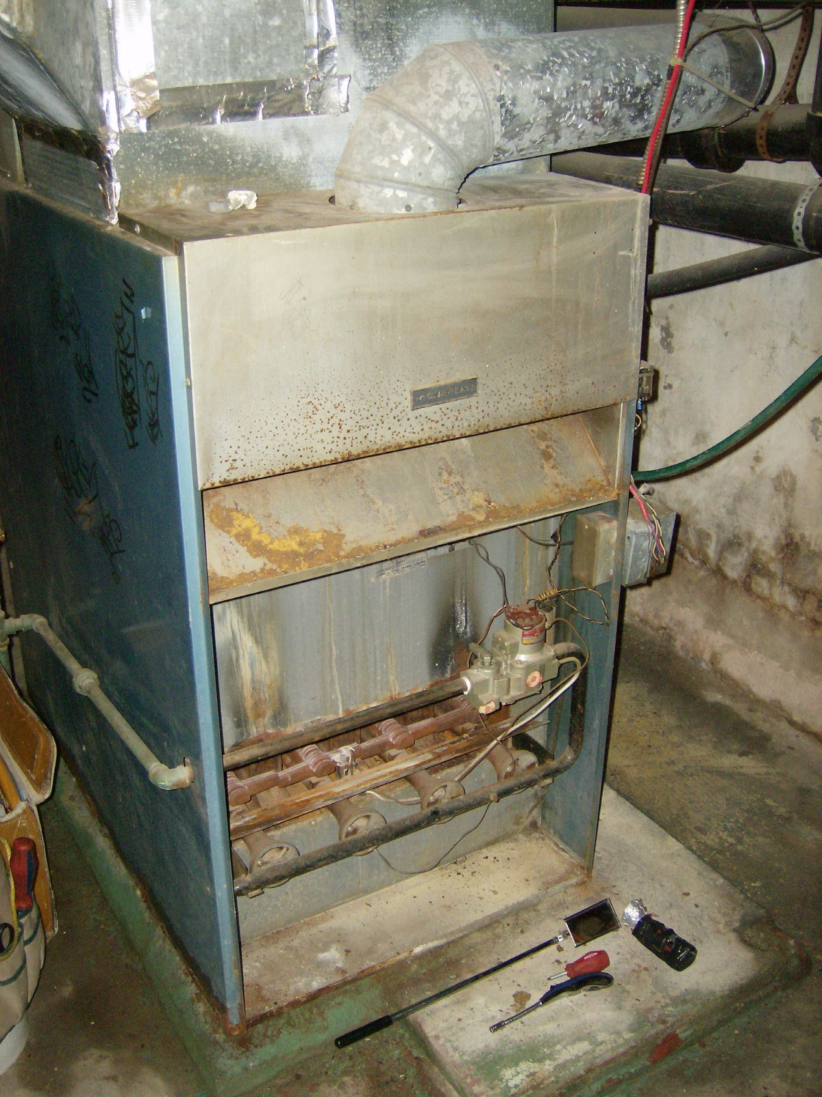 A rusted, dirty, old furnace that needs repair