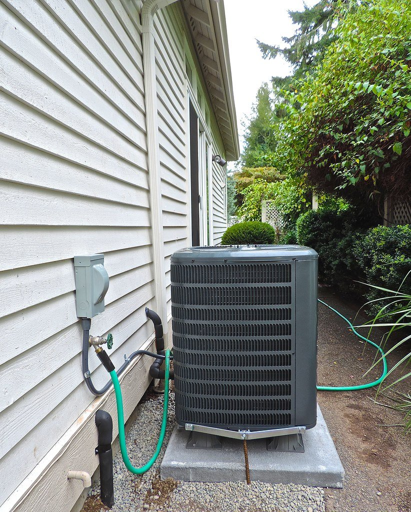 Heat pump system free of clutter or debris, sitting behind home