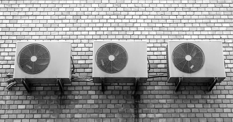 Mini-split systems line up against a brick wall